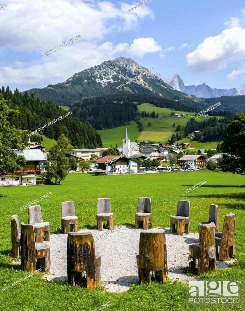 Stock Photo: A circle of wooden chairs mark one of the local powerspots near Filzmoos village. The village and Rotelstein complete the picture.
