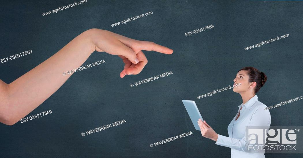 Imagen: Hand pointing at business woman holding a tablet against blue background.