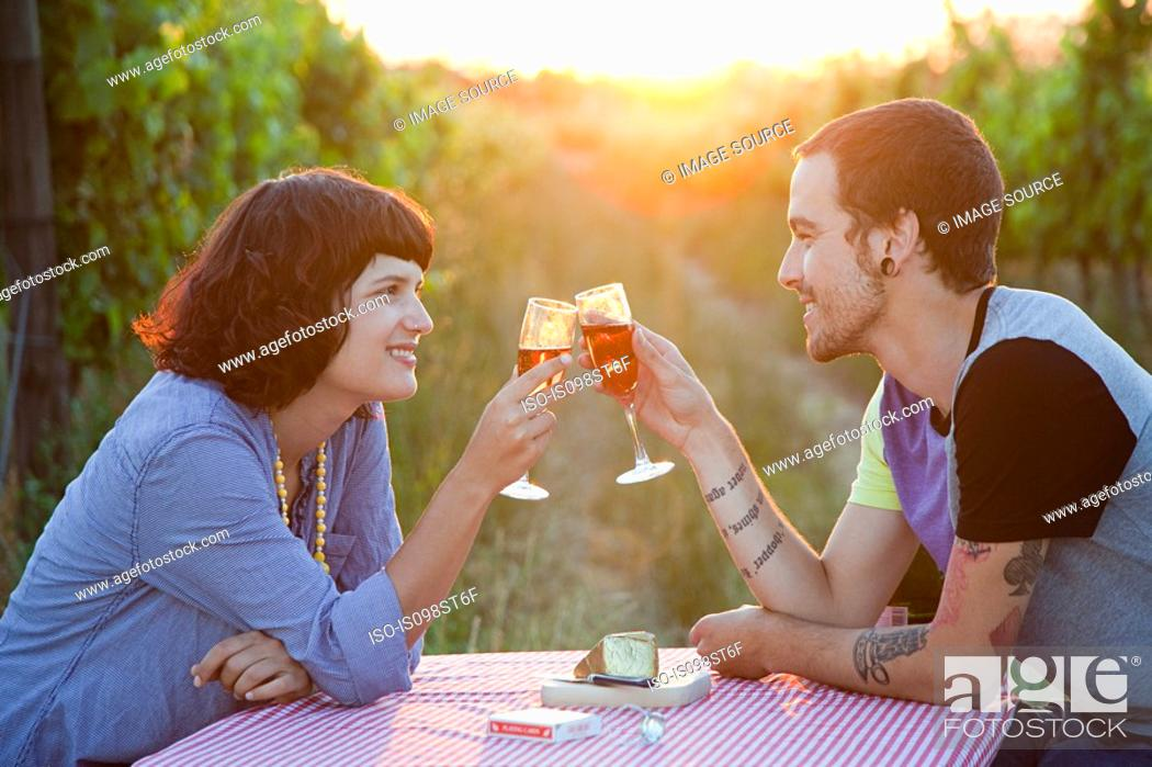 Stock Photo: Couple toasting with glasses of wine in field.