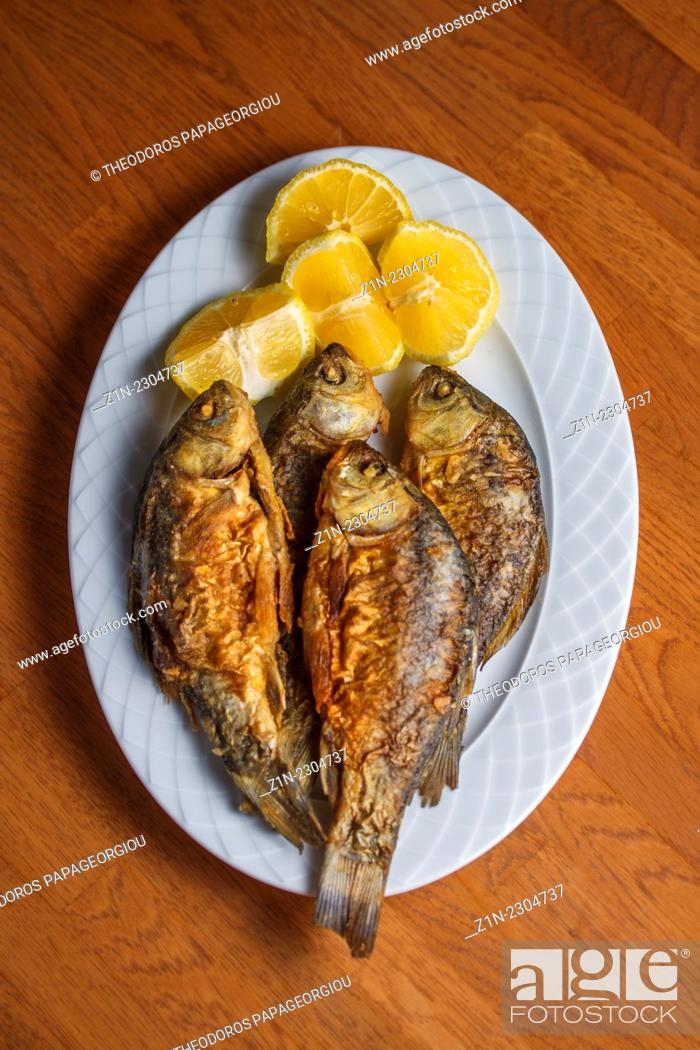 Stock Photo: A traditional Greek food dish with Red snapper and lemons. Peloponnese, Greece.