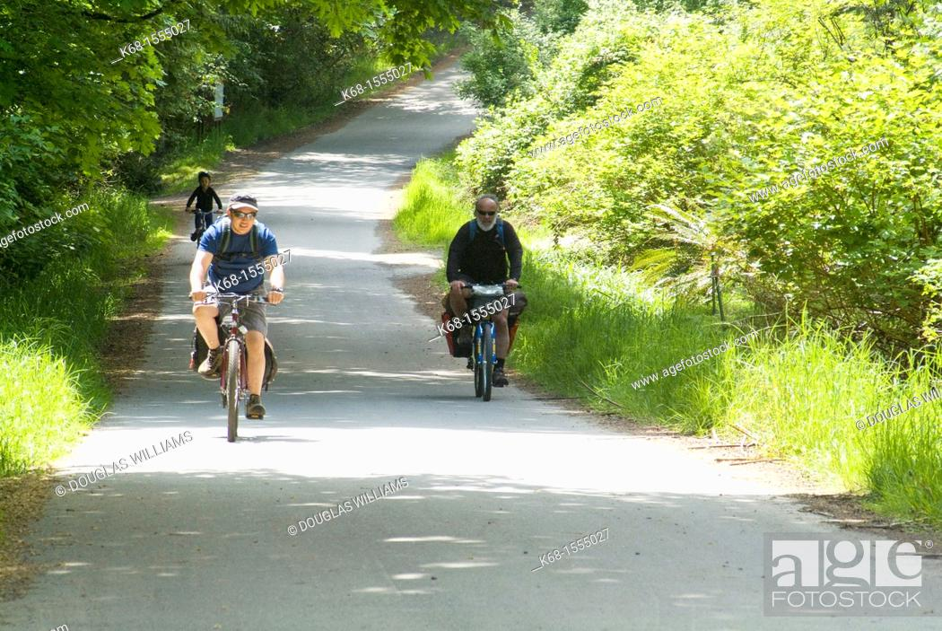 Stock Photo: three people bicycling on a country road on Saltspring Island, BC, Canada.