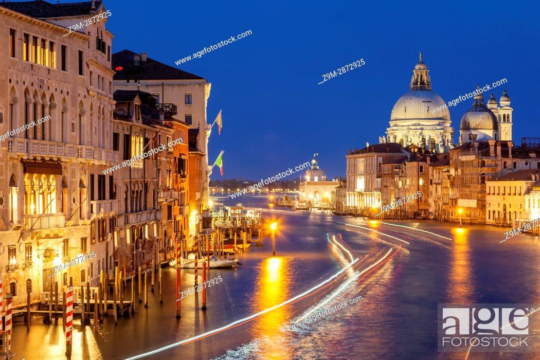 Stock Photo: Night falls on Grand Canal in Venice, Italy. Santa Maria della Salute church dome in the distance.