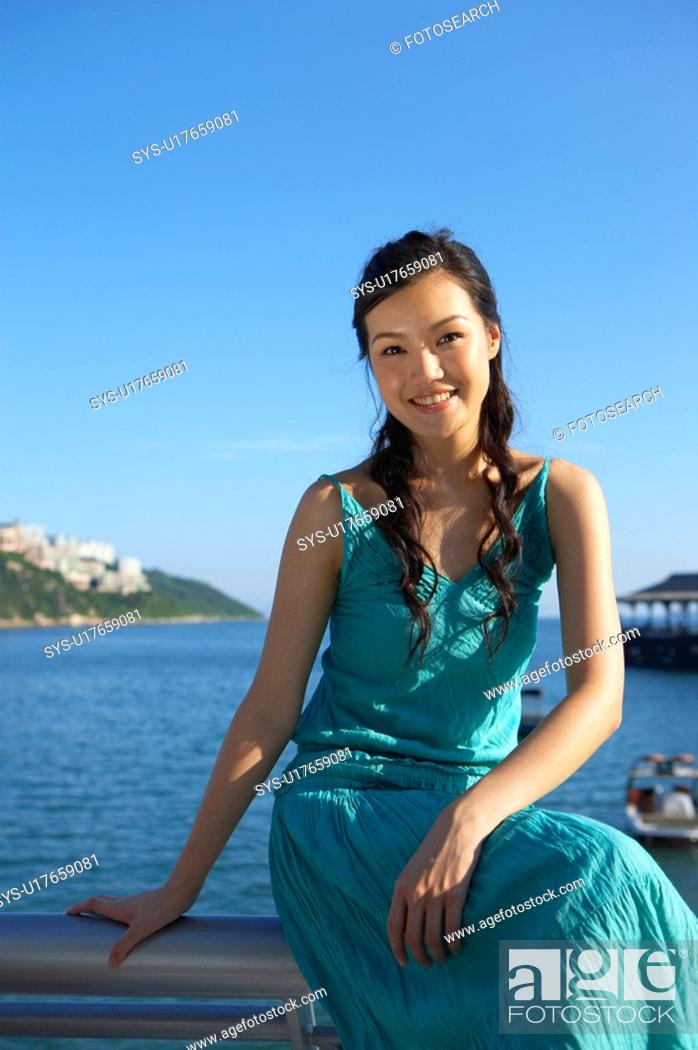 Stock Photo: Young Lady Sitting on Railing of Fence, Smiling.