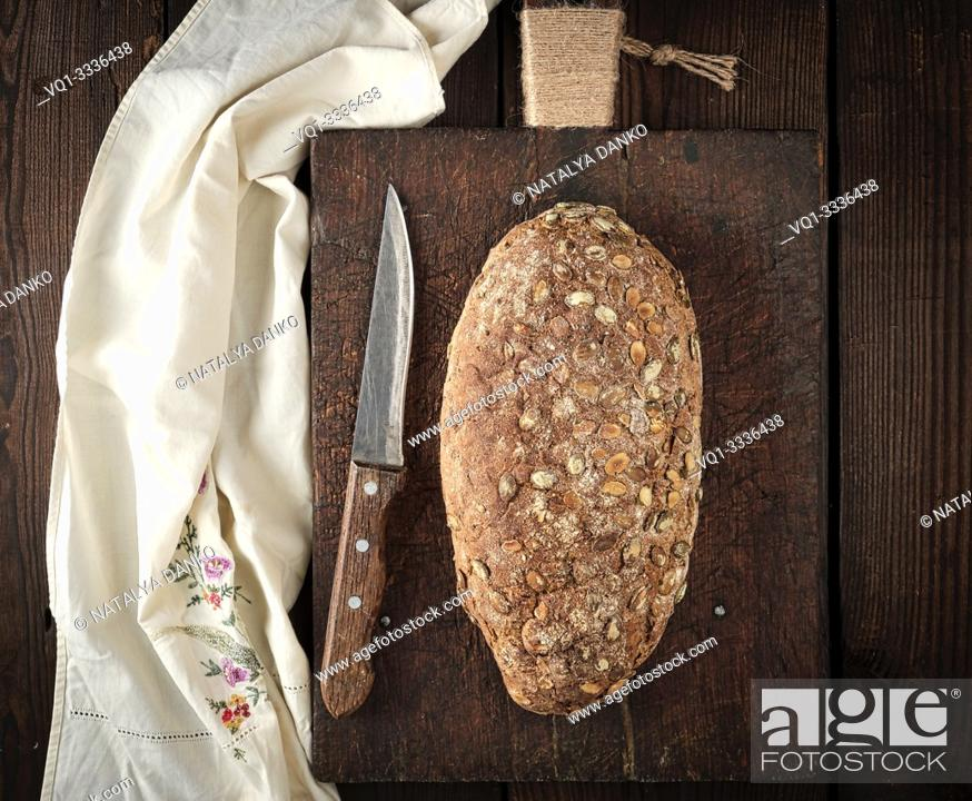 Stock Photo: baked oval bread made from rye flour with pumpkin seeds on a wooden cutting board , top view.