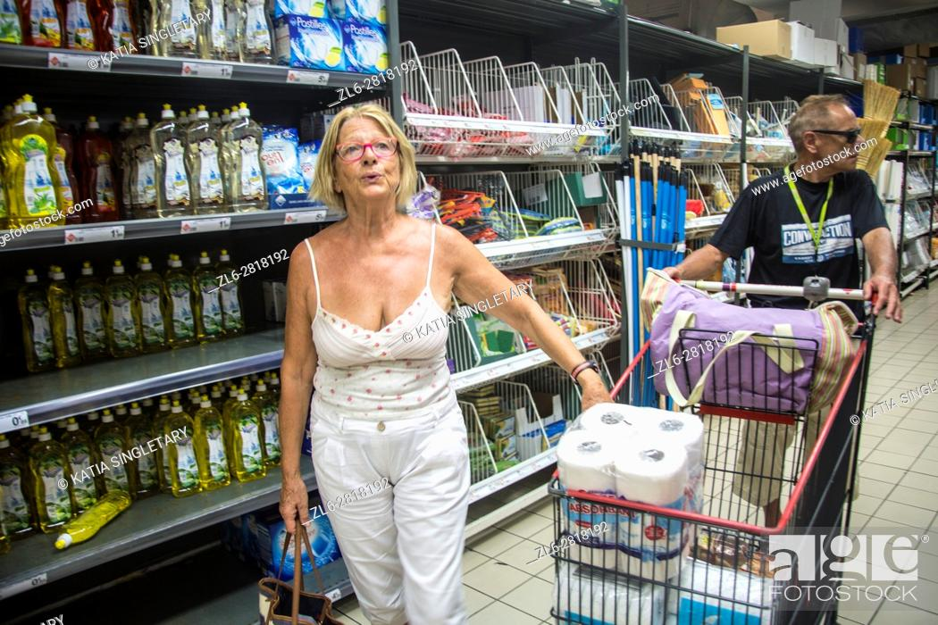 Stock Photo: Mature retired senor caucasian woman doing her grocery shopping on vacation while her husband push the cart.