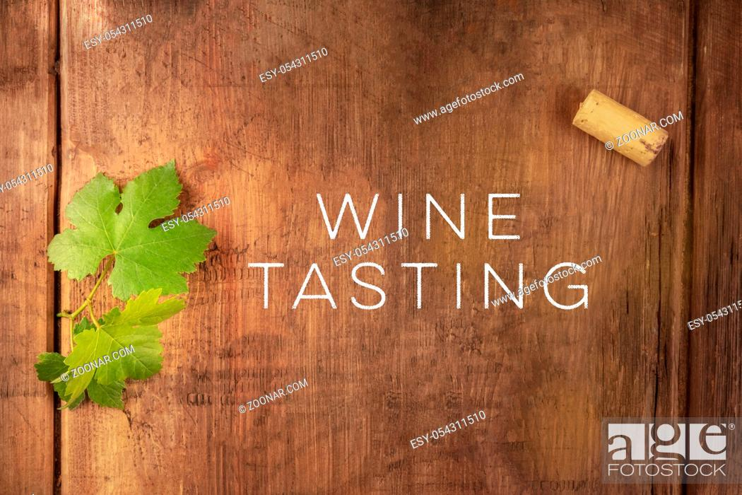 Stock Photo: Wine Tasting invitation design template with a vine leaf and a wine cork, shot from the top on a dark rustic wooden background with a place for text.