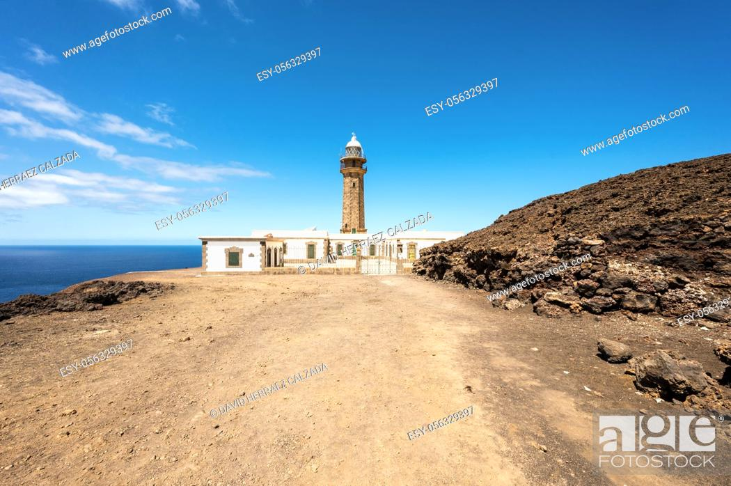 Stock Photo: Beautiful view of famous El Faro de Punta Orchilla lighthouse with red volcanic scenery and wide open sea on a sunny day, El Hierro, Canary Islands, Spain.