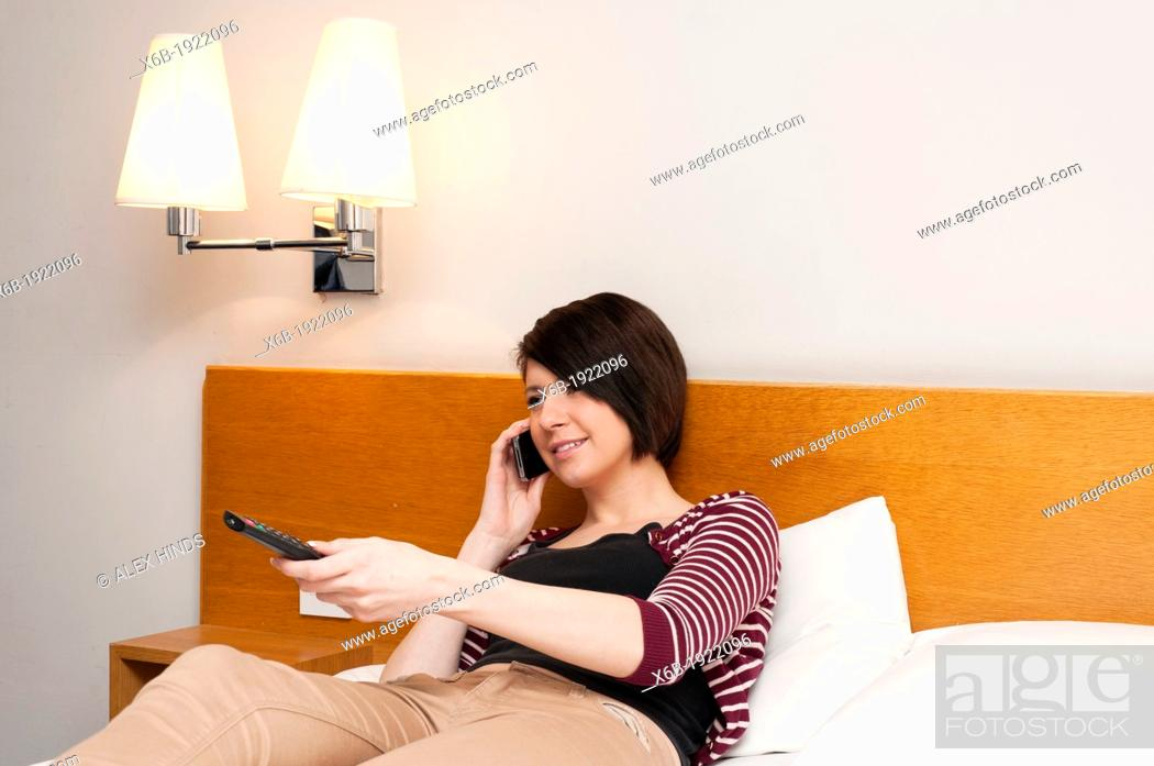 Stock Photo: Young woman teenager sitting on bed watching TV and talking on mobile phone.