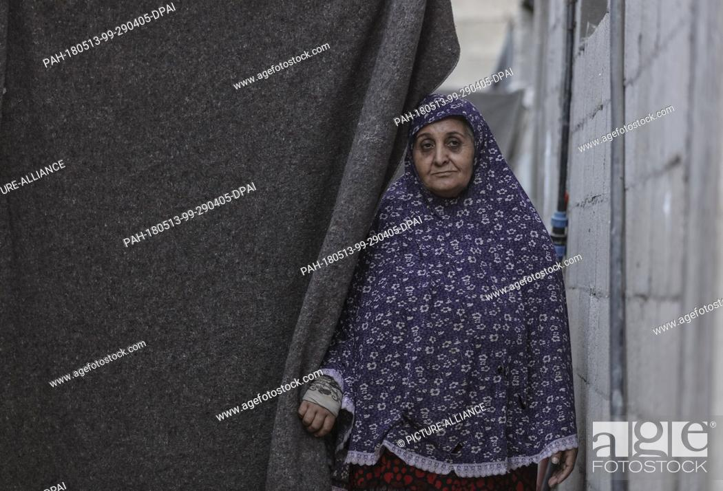 dpatop - A Palestinian refugee woman stands at the doorway
