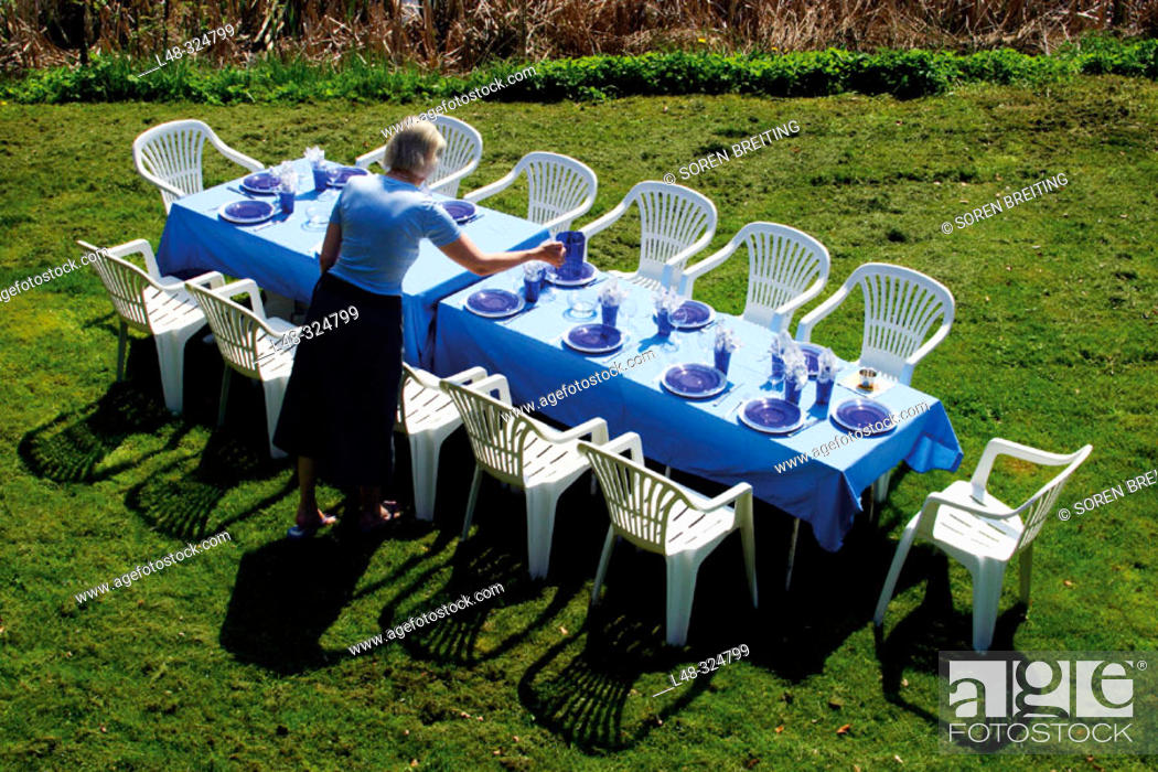 Stock Photo: Preparing the dining table outside in the garden on the lawn for a meal with blue plates and glasses, and blue tablecloth. Denmark, Scandinavia.