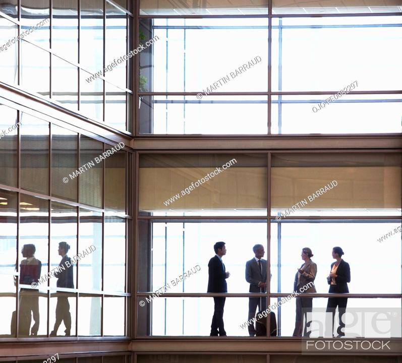 Stock Photo: Business people talking in modern office corridor.
