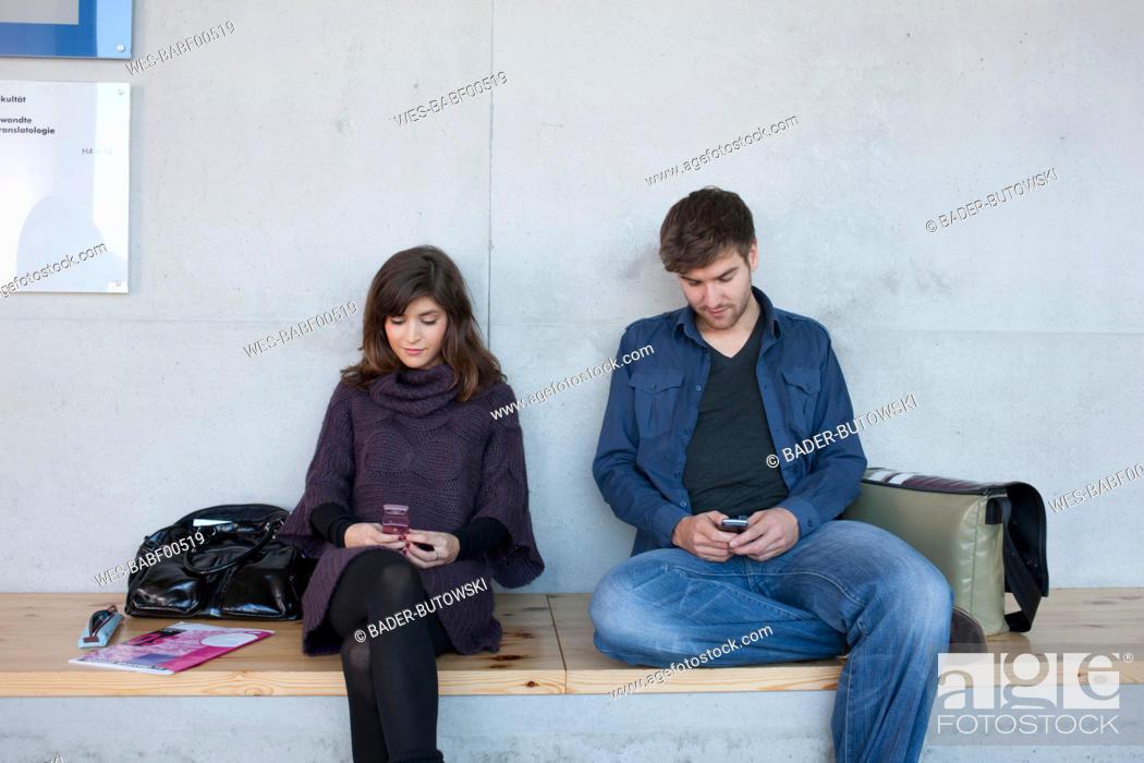 Stock Photo: Germany, Leipzig, University students sitting and using mobile phone.