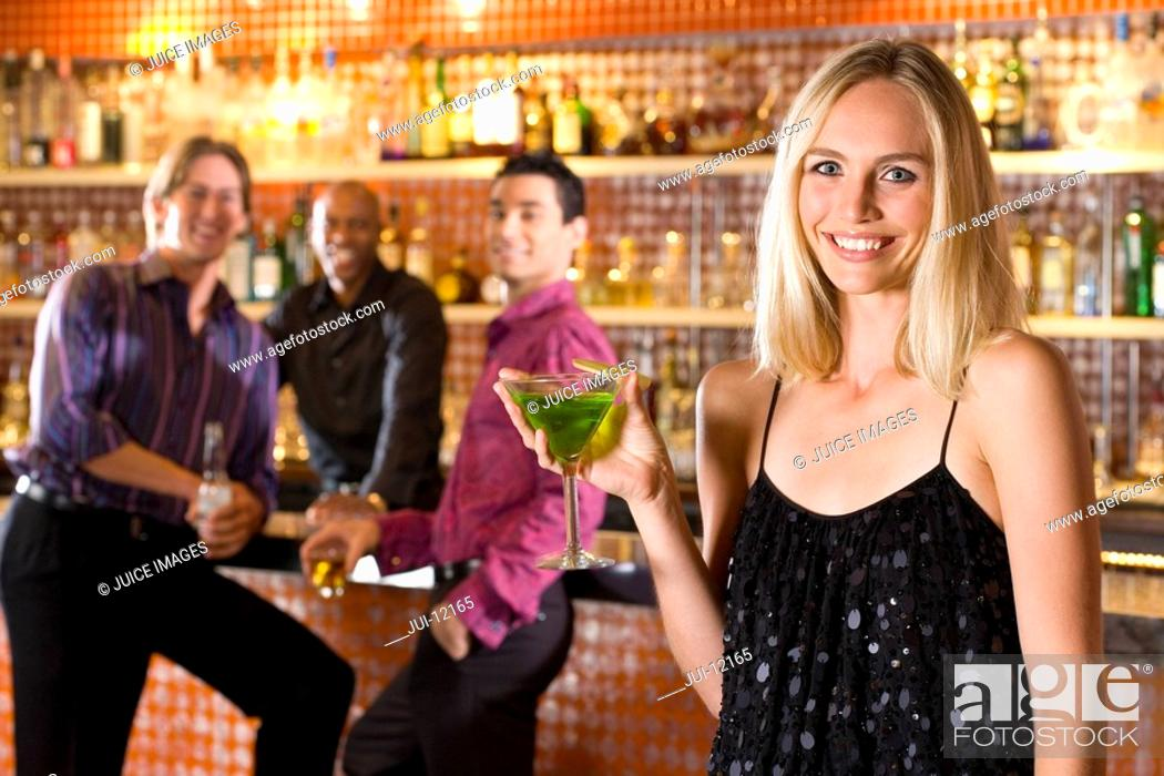 Stock Photo: Young man and friend at bar looking at woman with cocktail, smiling, portrait.