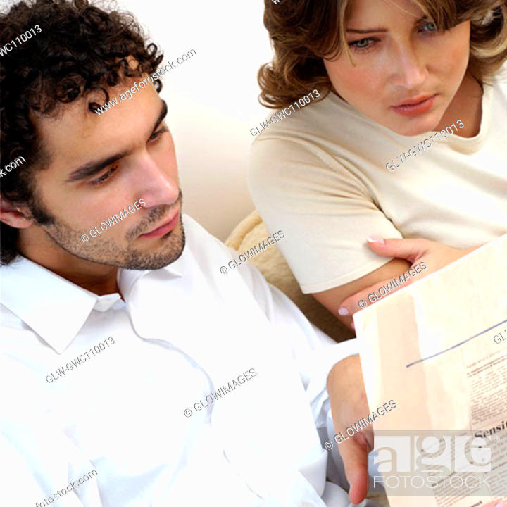 Stock Photo: High angle view of a young couple reading a newspaper.