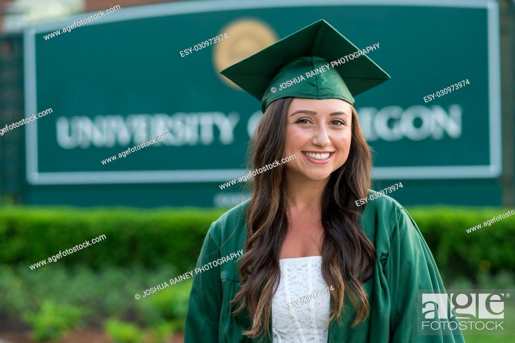 Stock Photo: Female graduating student in her cap and gown with a blurred out college school sign in the background on a university campus during the Spring in Oregon.