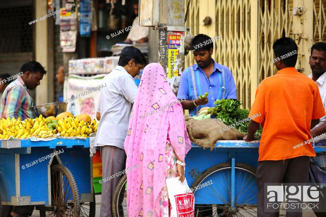 Stock Photo: Bangalore, India - October 23, 2016: Unknown married Indian couple buying green leaf vegetables from a street side seller in the Avenue road.