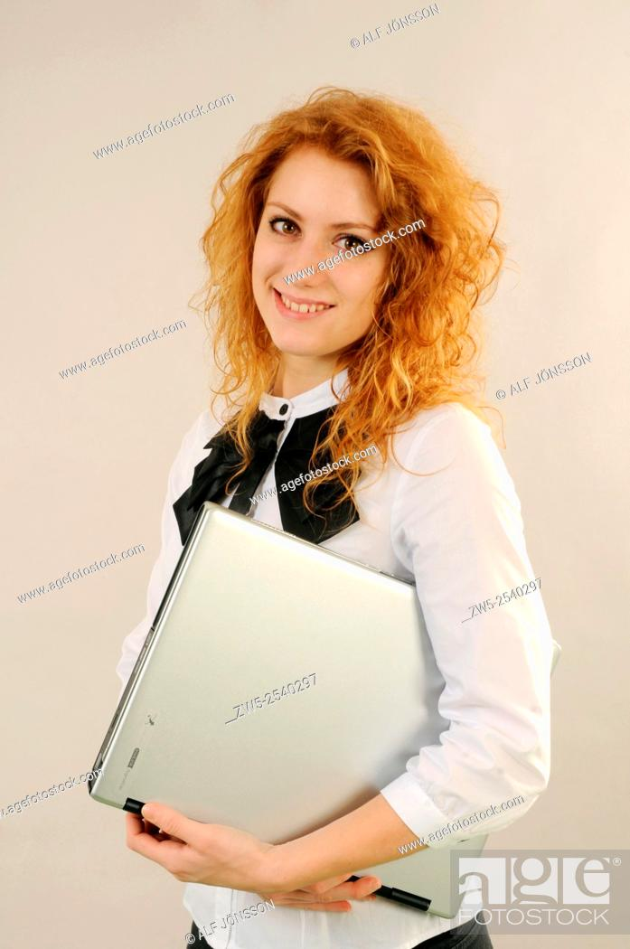 Stock Photo: Redhaired young woman standing with a computer.