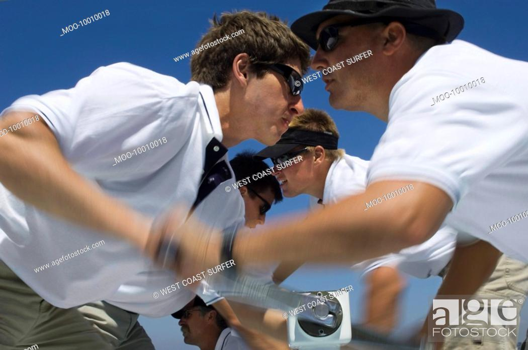 Stock Photo: Sailors operating windlass on yacht side view.