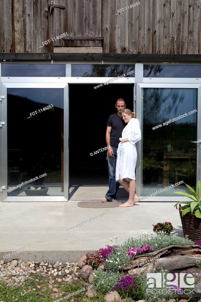 Stock Photo: A couple leaning against the doorway of their house in the morning.