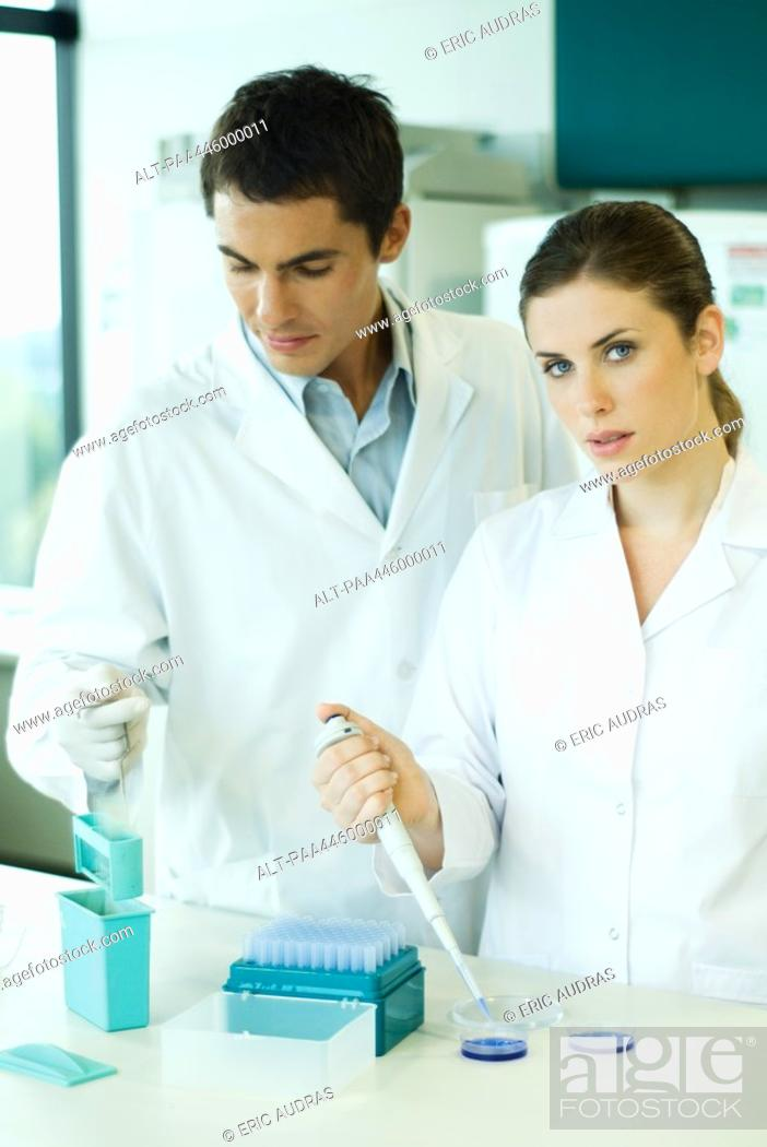 Stock Photo: Male and female lab workers standing side by side, woman looking at camera.