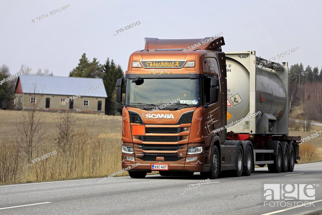 Stock Photo: Salo, Finland - April 5, 2019: Bronze Next Generation Scania R580 truck of AH Trans Oy hauls chemical liquid container along highway in Finland.