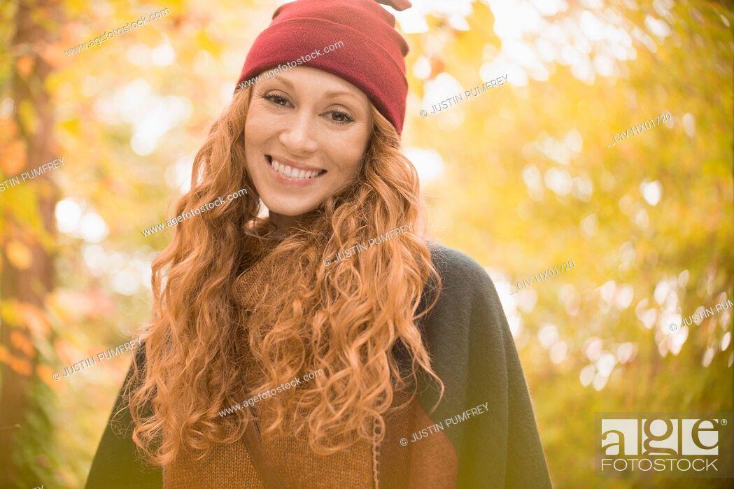 Stock Photo: Portrait smiling woman in stocking cap under autumn trees.