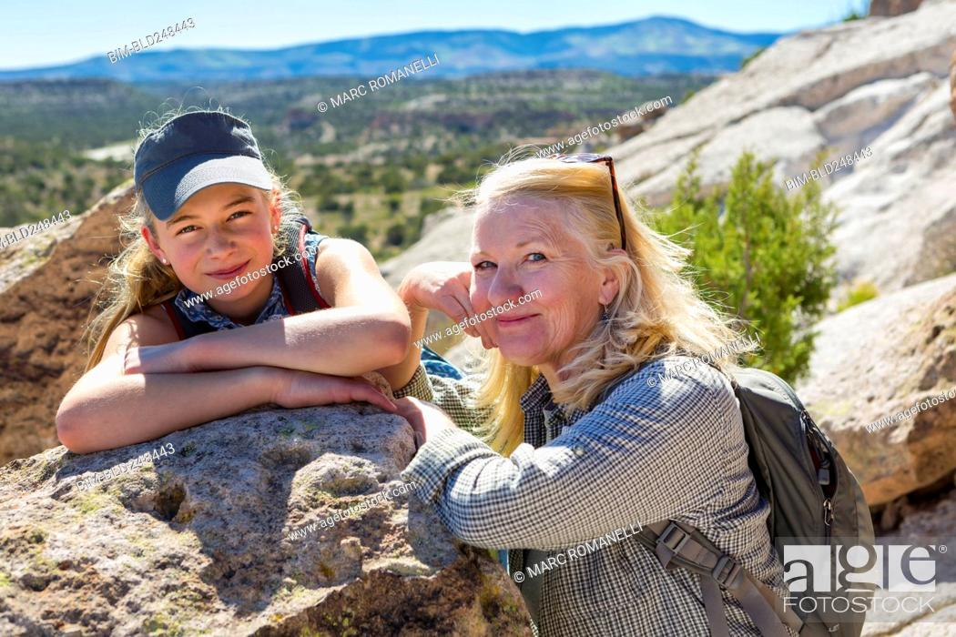 Stock Photo: Portrait of Caucasian grandmother and granddaughter leaning on rock.