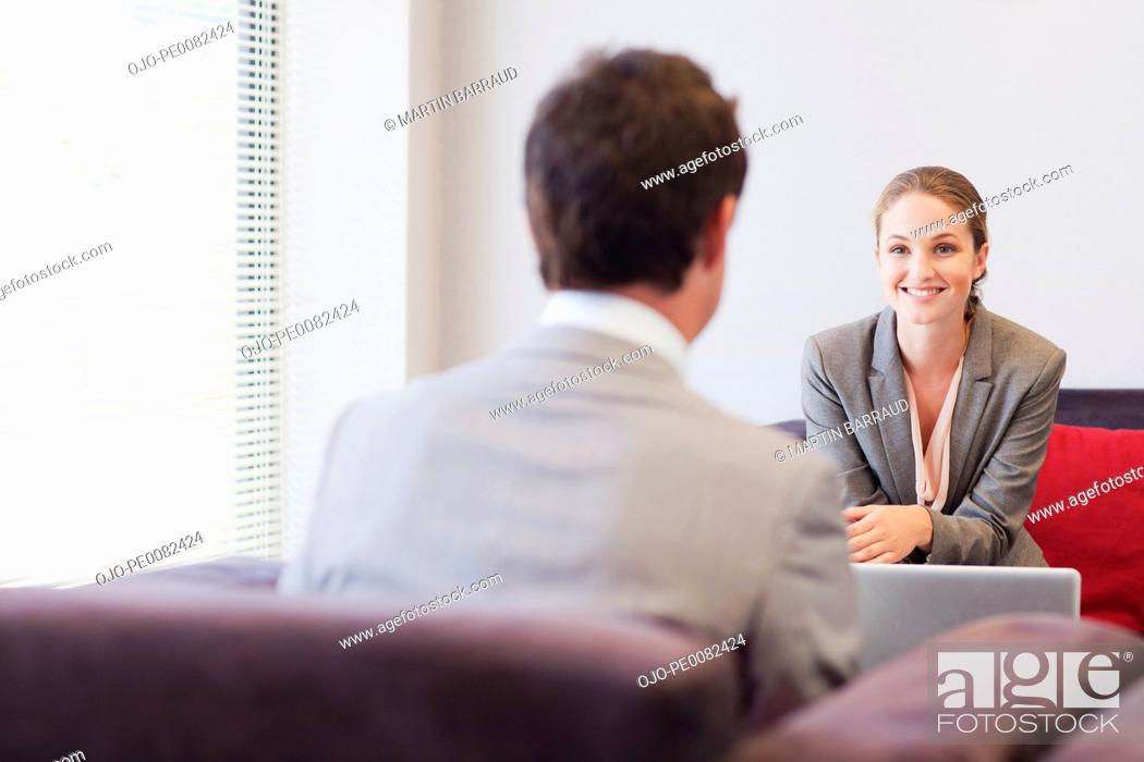 Stock Photo: Business people talking face to face in lobby.