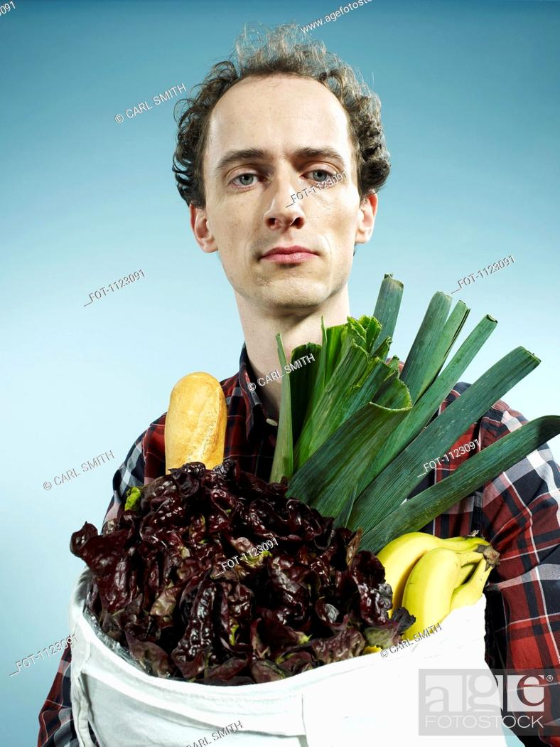 Stock Photo: A man carrying a bag of groceries.