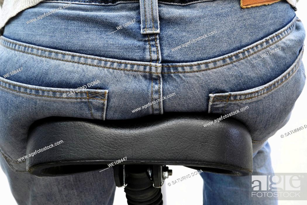 Stock Photo: person wearing jeans sitting on bicycle saddle.