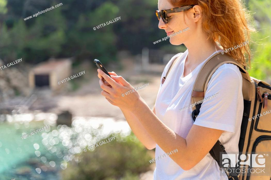 Stock Photo: Portrait of redheaded woman using smartphone.