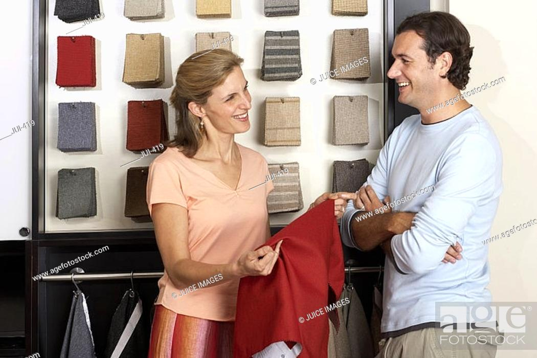 Stock Photo: Couple standing beside fabric swatch display in shop, woman holdind red textile sample, smiling.