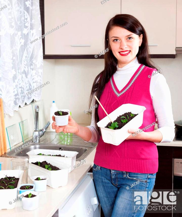 Stock Photo: Smiling woman with various seedlings at home kitchen.