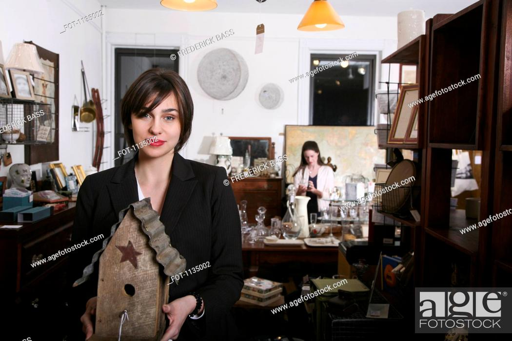 Stock Photo: A woman holding an old birdhouse in an antiques shop.
