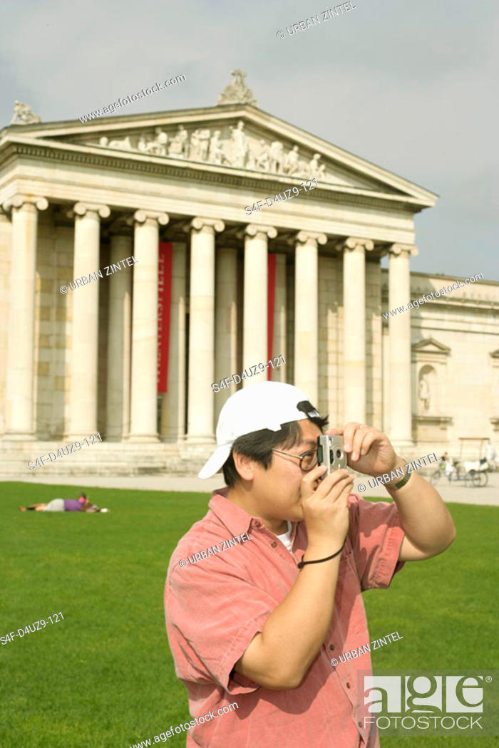 Stock Photo: Asian man with a camera standing in front of an antique museum.
