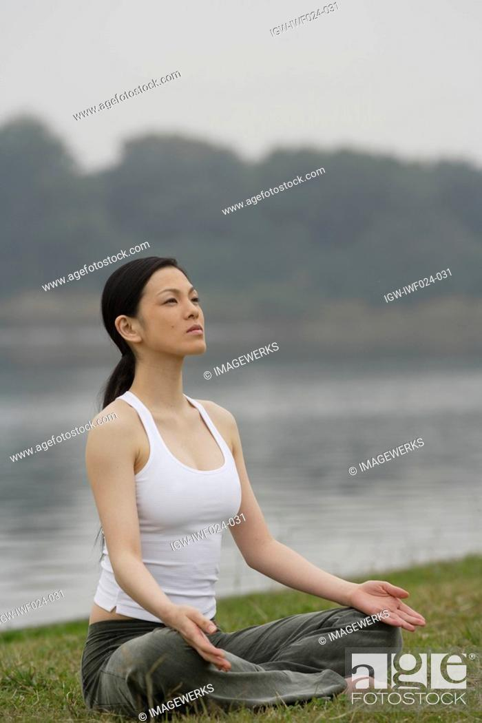 Photo de stock: Front view of a woman in lotus position.