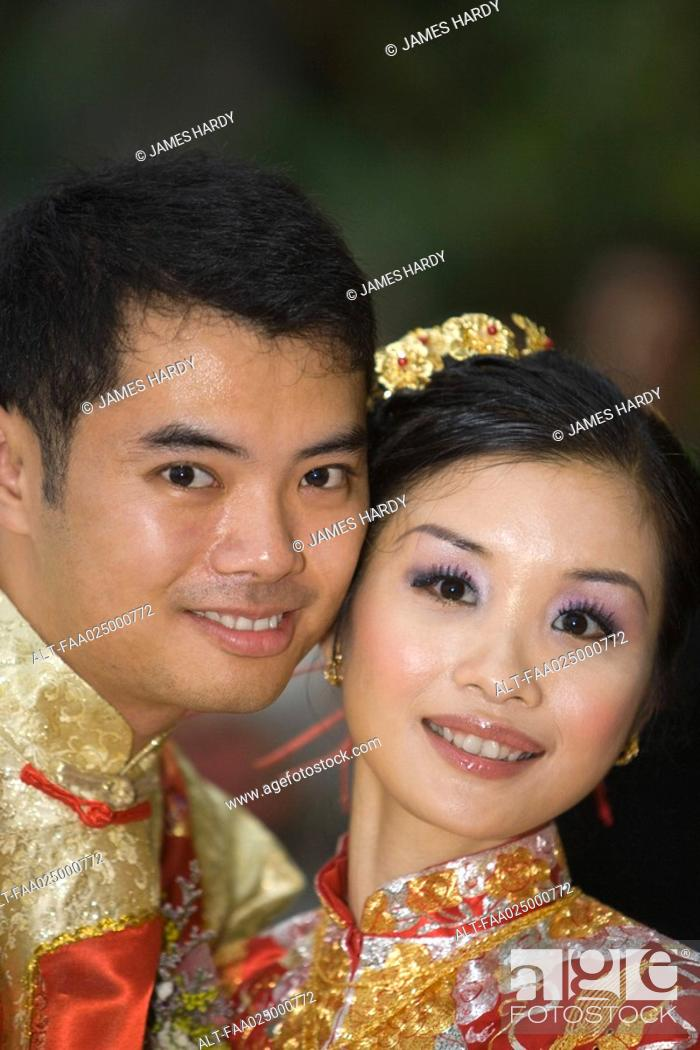 Stock Photo: Newlyweds in traditional Chinese clothing, cheek to cheek, smiling at camera.