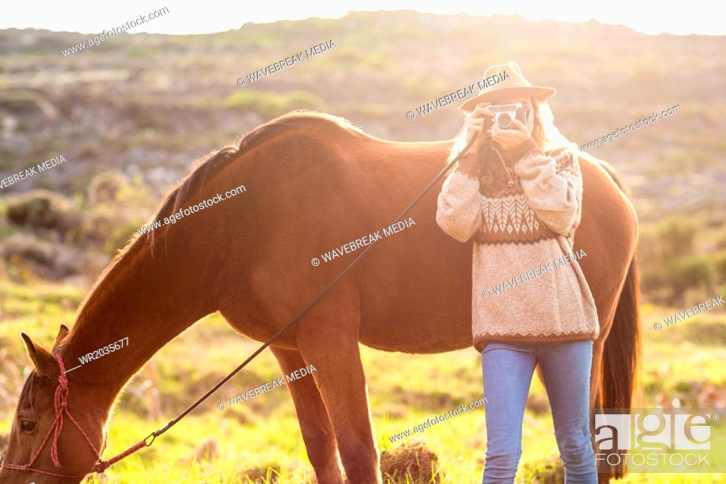 Stock Photo: Young woman with her horse taking photo.