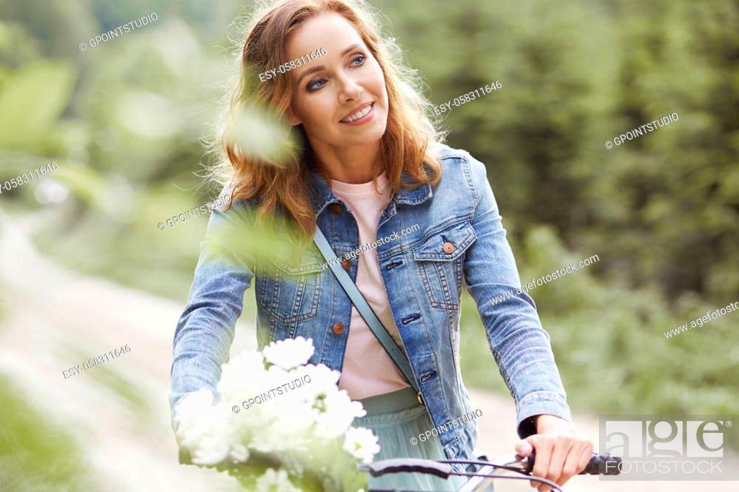 Stock Photo: Beautiful woman riding a bike.