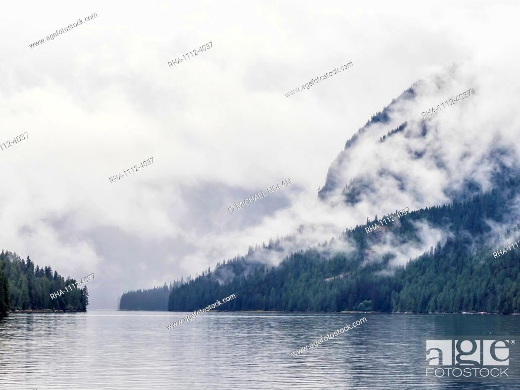 Stock Photo: Low lying clouds shroud the mountain tops in Misty Fjords National Monument, Southeast Alaska, United States of America.