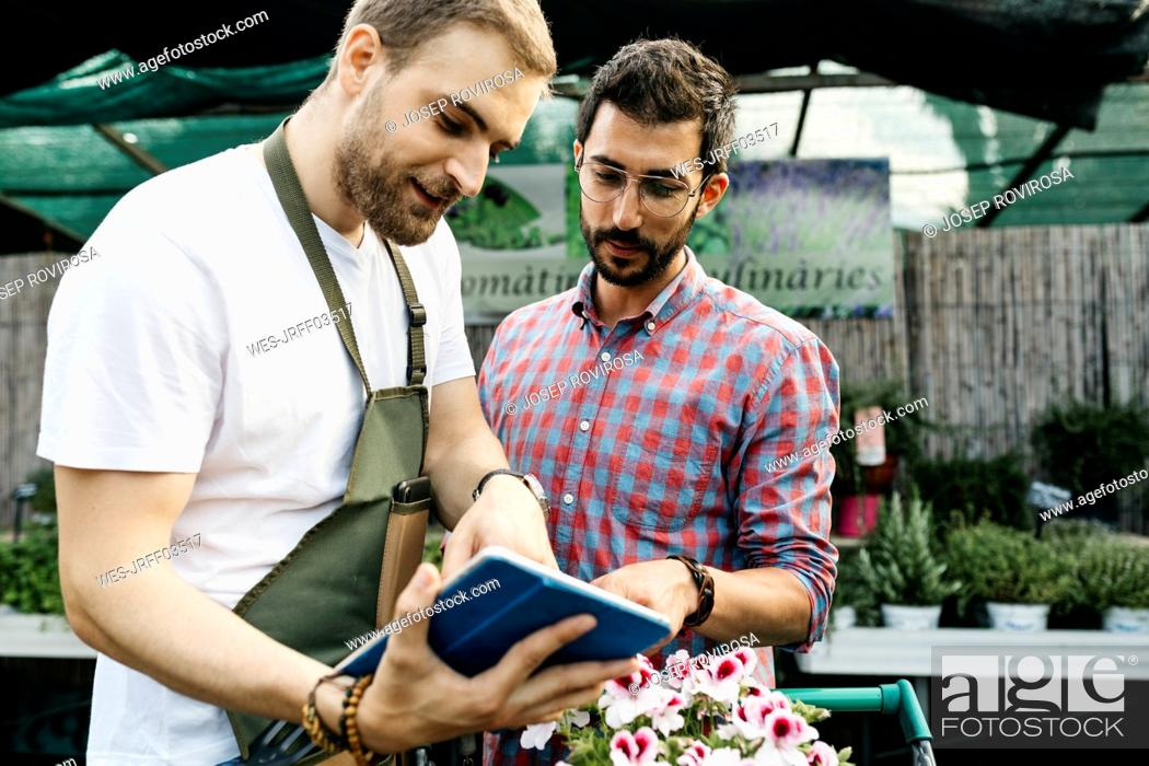Stock Photo: Worker with tablet in a garden center advising customer.