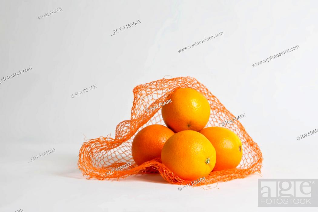 Stock Photo: A pile of oranges in an open net bag.