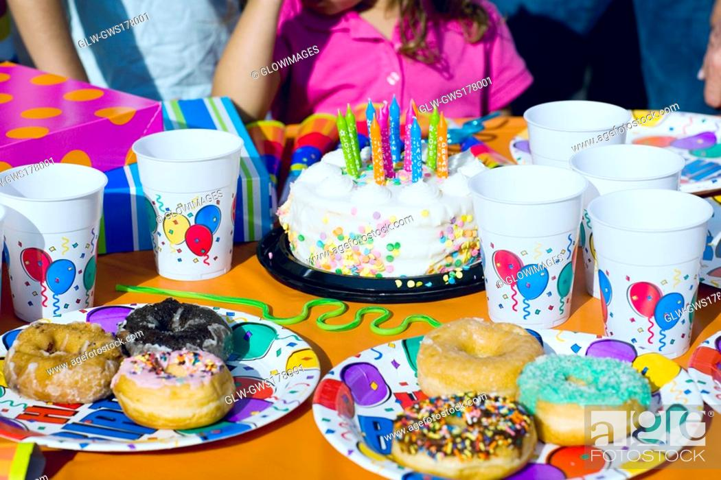 Stock Photo: Birthday cake and donuts with presents on a table.
