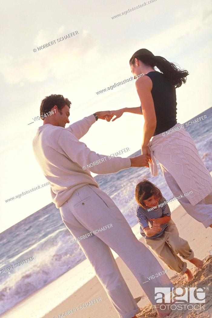 Stock Photo: beach-scene, full-figure, dark-haired family with 4 year old daughter is playing bare feeted at the beach, all are wearing khaki trousers  - GERMANY, 07/04/2004.