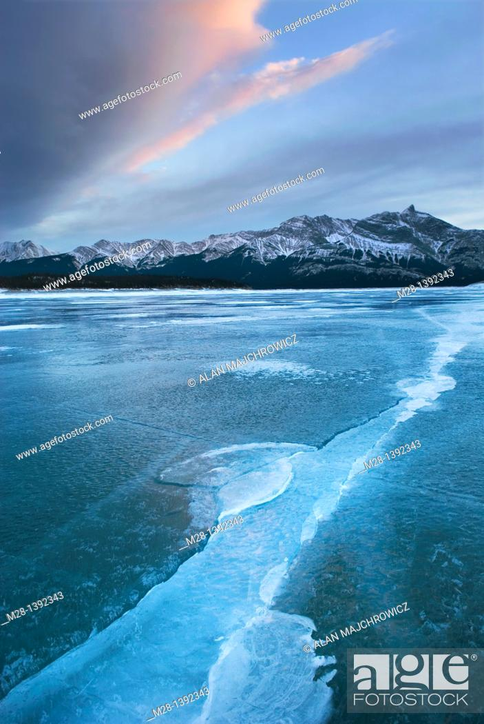 Stock Photo: Clouds glowing in a winter sunset over the wind polished ice of Abraham Lake, Alberta Canada.