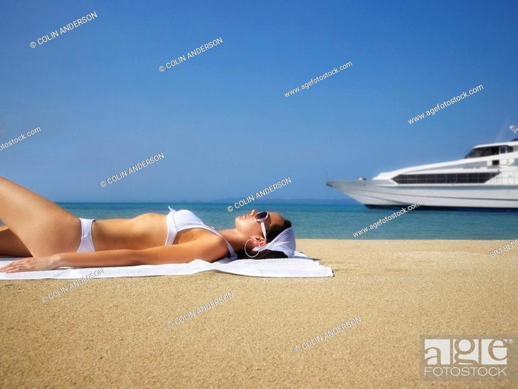 Stock Photo: Pacific Islander woman sunbathing on beach.