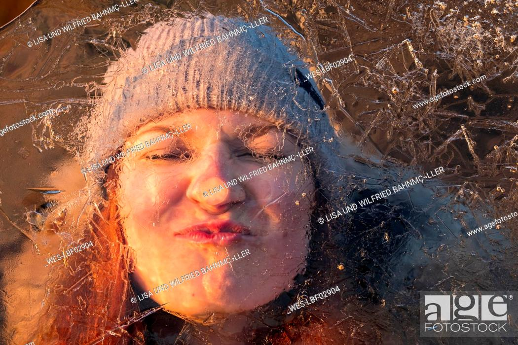 Stock Photo: Portrait of teenage girl pulling funny face behind ice-covered surface.