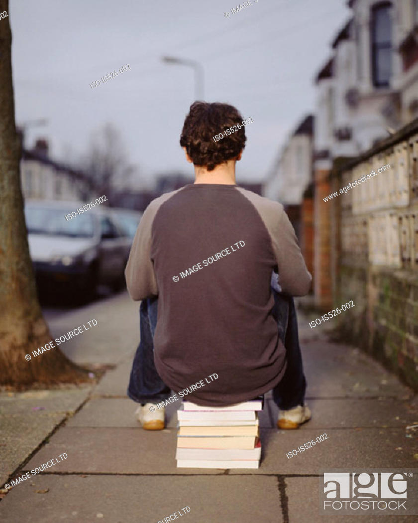 Stock Photo: A young man sitting on a pile of books.