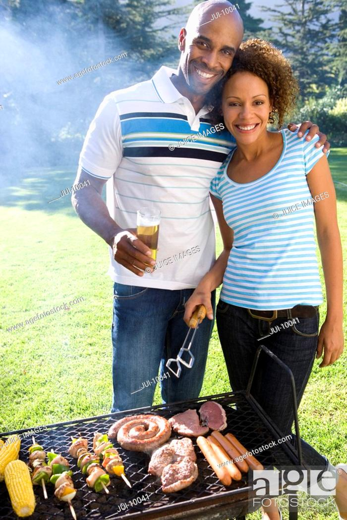 Stock Photo: Man embracing woman by barbeque, smiling, portrait.
