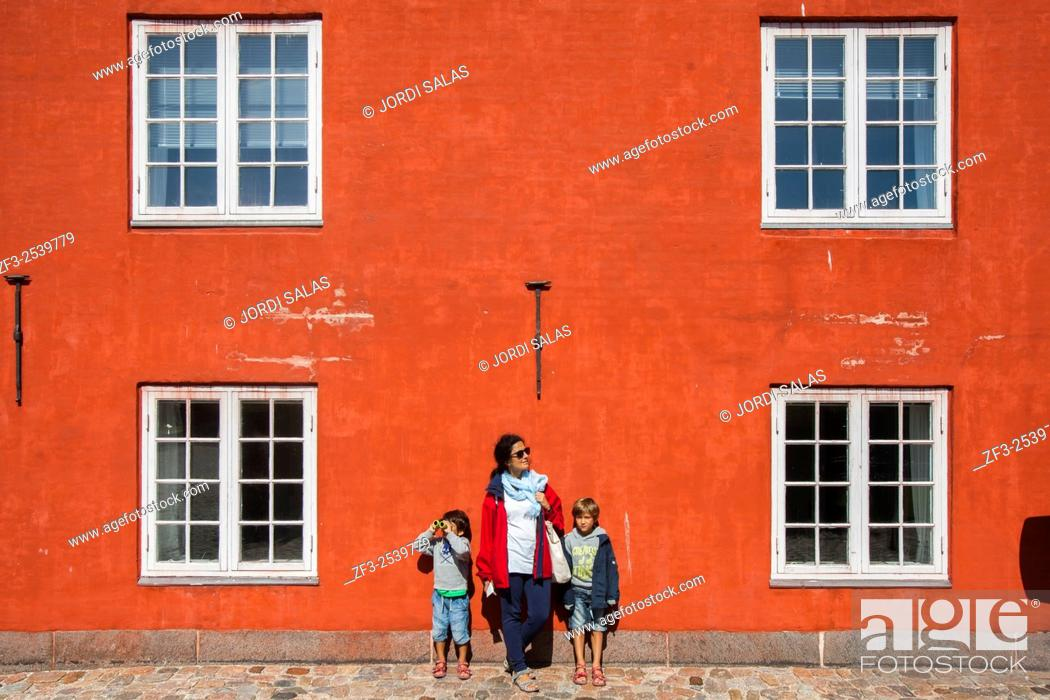 Stock Photo: Mother and two child on a red wall. Kastellet, Copenhagen. Denmark.